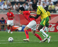 Korea Republic's Jae Jin Cho (left) is chased by Togo's Dare Nibombe (2). Korea Republic defeated Togo 2-1 in their FIFA World Cup Group G match at the FIFA World Cup Stadium, Frankfurt, Germany, June 13, 2006.