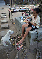 Bali, Indonesia.   Young Girl Eating Lunch while her Pet Dog Looks On.  Tenganan Village.