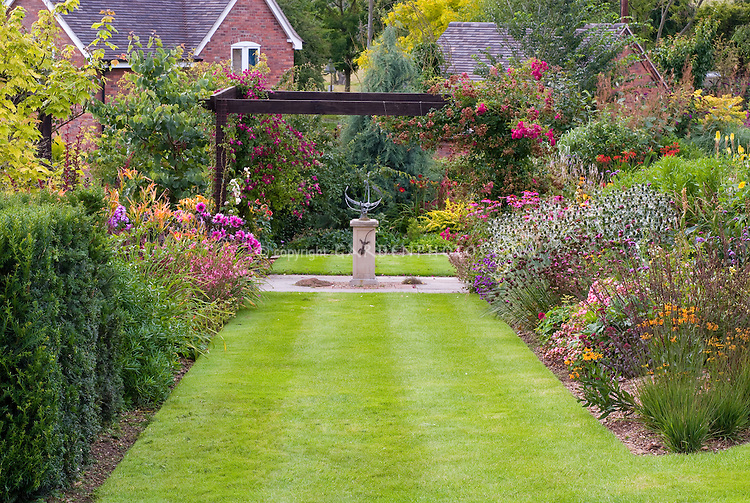 Manor Farm formal cottage garden - view of garden beds, ornamental armillary sundial, brick house, lawn grass, climbing roses, lush flowers, symmetrical formal garden design style, wide lawn grass path, arbor trellis with red garden roses, evergreens, mixture of plantings