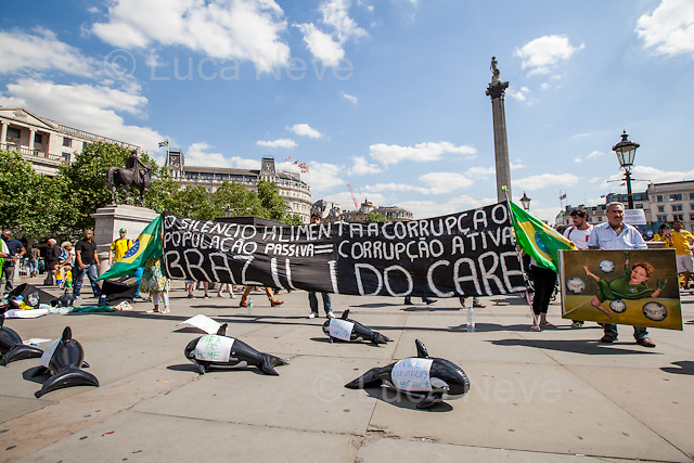 """""""O Silencio Alimenta A Corrupcao. Populacao Passiva = Corrupcao Ativa. Brazil I Do Care"""".<br /> Kaya Mar (Painter and political caricaturist).<br /> <br /> London, 12/06/2014. Today, on the day of the opening ceremony of the 20th World Cup of Football in Sao Paolo (Brasil), a group of Brasilian people held a demonstration in Trafalgar Square to raise awareness of the problems that are still affecting their country (see photo captions) and in support and solidarity with the protests currently happening in Brasil. Meanwhile, the official """"Brazil Day"""" organised by the Mayor of London was held without disruption in the main square."""