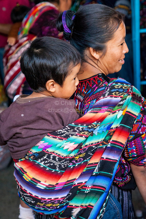 Chichicastenango, Guatemala.  Quiche (Kiche, K'iche') Mother Carrying Young Boy on her Back.