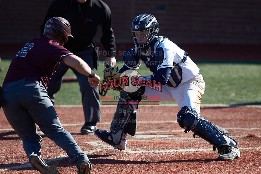Wingate Bulldogs catcher Logan McNeely (18) waits for the arrival of Jakob Divers (2) of the Concord Mountain Lions at home plate at Ron Christopher Stadium on February 2, 2020 in Wingate, North Carolina. The Mountain Lions defeated the Bulldogs 12-11. (Brian Westerholt/Four Seam Images)