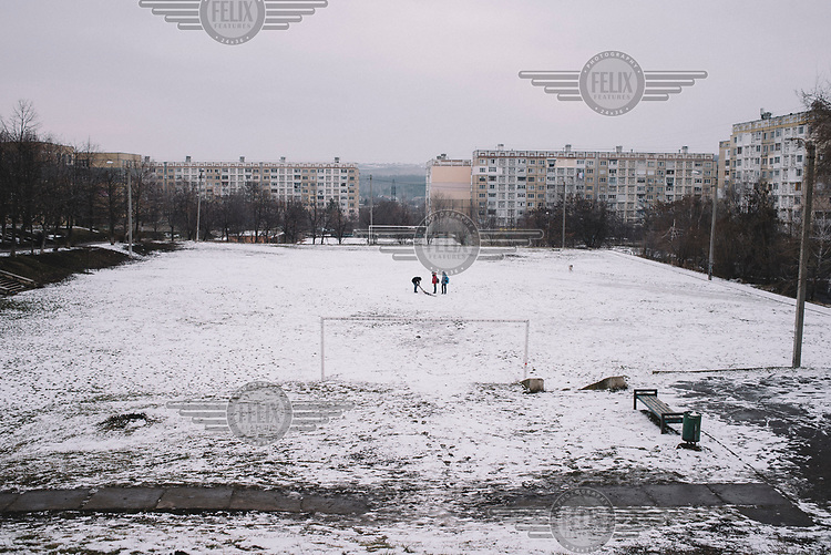 A group of people on a snow covered a football pitch in the Ciocana district.