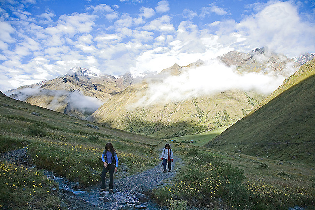 TWO FEMALE HIKERS MAKING THEIR WAY UP THE SALKANTAY PASS IN THE PERUVIAN ANDES