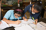 Science lab at public school for the gifted two female students entering data from experiment measuring range of motion Grade 5;