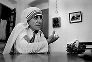 """Calcutta, India. April 04, 1975. Mother Teresa talking and listening to her staff inside her Kalighat Home for the Dying in Calcutta. The first Home for the Dying opened in 1952 and was a free hospice for the poor. Mother Teresa (Agnes Gonxha Boyaxihu) the Roman Catholic, Albanian nun revered as India's """"Saint of the Slums,"""" was awarded the 1979 Nobel Peace Prize."""
