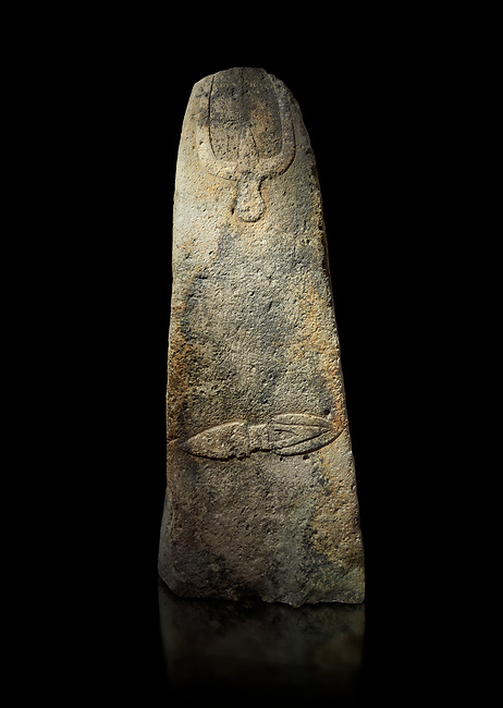 Late European Neolithic prehistoric Menhir standing stone with carvings on its face side. The representation of a stylalised male figure starts at the top with a long nose from which 2 eyebrows arch around the top of the stone. below this is a carving of a falling figure with head at the bottom and 2 curved arms encircling a body above. at the bottom is a carving of a dagger running horizontally across the menhir.  Excavated from Piscina 'E Sali V site,  Laconi. Menhir Museum, Museo della Statuaria Prehistorica in Sardegna, Museum of Prehoistoric Sardinian Statues, Palazzo Aymerich, Laconi, Sardinia, Italy. Black background.