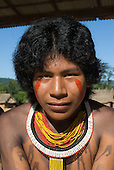 Pará State, Brazil. Aldeia Pukararankre (Kayapo). Nyere Kayapo, a young warrior with red urucum face paint and bead necklaces.
