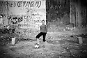 Iraq 2010 .Young boy playing football on a waste ground in Erbil  .Irak 2010 .Jeune kurde jouant au football sur un terrain vague d'Erbil