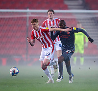 29th December 2020; Bet365 Stadium, Stoke, Staffordshire, England; English Football League Championship Football, Stoke City versus Nottingham Forest; Sam Clucas of Stoke City and Samba Sow of Nottingham Forest chase a loose ball in the fog