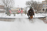 Kenny Baker with the Park and Recreation Sanitation Department blow the snow, Sunday February 1, 2021, off the sidewalks around the Bentonville Square. Snow is expected to end this morning and another snow fall is expects Wednesday.<br /> (NWA Democrat-Gazette/Spencer Tirey)
