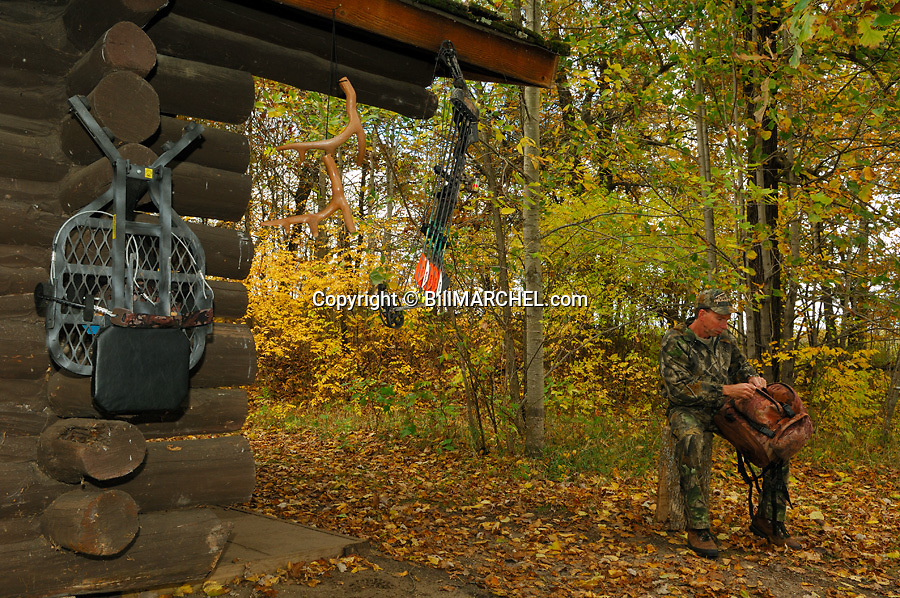 00105-041.13 Bowhunting (DIGITAL) Archer ckecks gear while at hunting shack.  Deer stand, backpack, rattling antlers, Realtree Camo.  H2F1