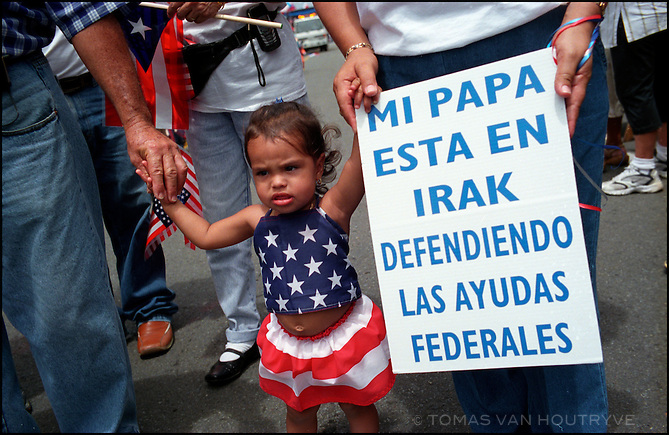 """A Puerto Rican girl carries a sign that says """"My father is in Iraq defending federal welfare,"""" during a U.S. Indenpendence Day parade on July 4, 2003 in San Juan in the United States territory of Puerto Rico. Residents of the island depend economically on the island?s unusual relationship with the United States. About 60% of the residents of the island are eligible for federal welfare. Over 10,000 Puerto Ricans serve in the U.S. military."""