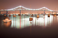 Boats gently sway on their moorings in the reflection of the Newport Bridge
