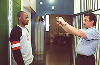 Switzerland. Bern. Regionalfgefängnis. Jail. Detention awaiting trial (commital for trial or pending trial). Loss of liberty. The prison warder Mr. Hugi takes a picture for the registration card of the prisoner Mr. K. K. ( a black man who is an asylum seeker from Africa). Model Released. © 2005 Didier Ruef