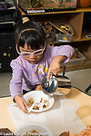 Preschool 3-4 year olds mealtime girl pouring own milk on cereal using left hand