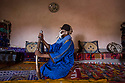 """Morocco - Aït Benhaddou - Jamal Kashir, 29, sits in his house wearing the props he used on the movie sets. Jamal works as a carpet vendor and background actor in Aït Benhaddou, a village 30 kms from Ouarzazate. Thanks to its perfectly preserved Kasbah, the village has provided the setting for several renowned movies, including Lawrence of Arabia, The Jewel of the Nile, 007 – The Living Daylights, Babel, Gladiator, Queen of the Desert and Prince of Persia. Kashir still remembers all the famous actors who passed here. """"Russell Crowe was the best, he used to spend time to visit the village after the end of the shootings"""" he remembers."""