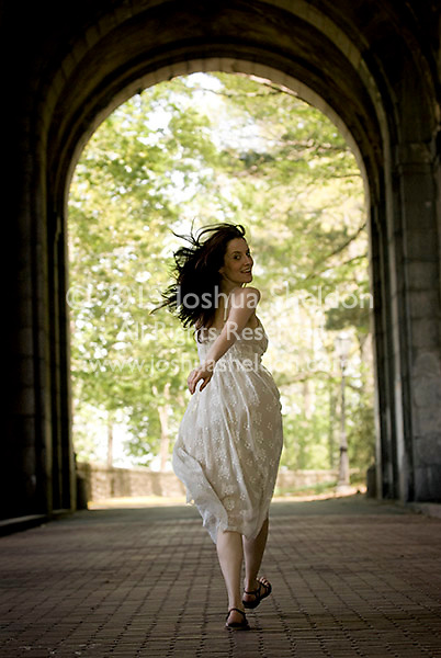 Woman running towards end of tunnel, rear view