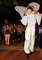 Walking on stilts, Kristen Greco, of the Carpetbag Brigade, takes part in the Parade of Little Angels Saturday night. The event was part of All Souls Procession festivities and took place at the downtown main library, 100 North Stone Ave.