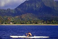 Man paddling one-man canoe off  Hanalei Beach, Hanalei Bay, North Shore, Kauai, Hawaii