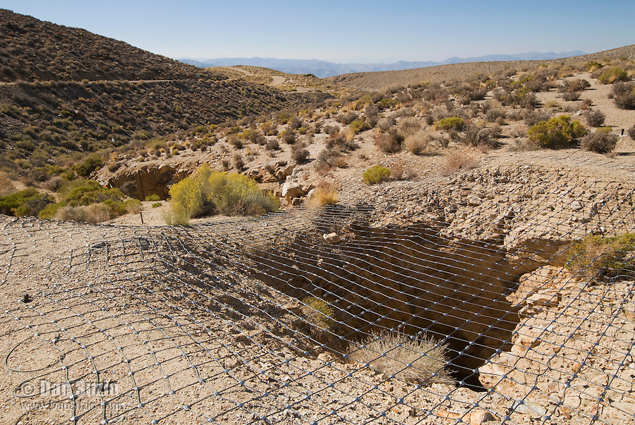 Abandoned mine opening, covered by wire mesh, at Skidoo, a gold-mining boomtown in the Panamint Range on the west side of Death Valley. At its peak in 1907 the town had 700 residents. Death Valley National Park, California.
