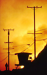 Along Pacific Coast Highway, Nov. 1993 south of Malibu a resident stands near a life guard shack on the beach as the hills are engulfed.