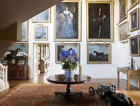 The private wing is accessed by a light-filled double-height entrance hall lined with gilt-framed portraits and landscapes