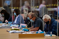 Pictured: A man counts the ballot papers during the Swansea West and South West Wales Regional Election Count at Brangwyn Hall in Swansea, Wales, UK. Friday 07 May 2020