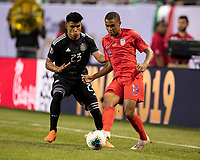 CHICAGO, IL - JULY 7: Reggie Cannon #14 passes the ball in front of Jesus Gallardo #23 during a game between Mexico and USMNT at Soldiers Field on July 7, 2019 in Chicago, Illinois.