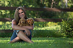 Young woman and golden retriever puppies