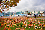 Biking Stanley Park.  The Skyline of downtown Vancouver, BC is seen from Stanley Park.  In urban Stanley Park, the promenade takes walkers, bikers, and bladers past the downtown skyline and lush natural gardens.