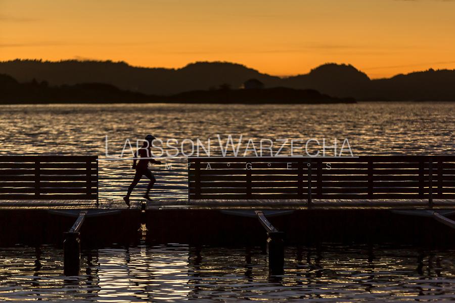 Female runner at sunset running across a jetty, West Sweden, Sweden - Västsverige, Sverige
