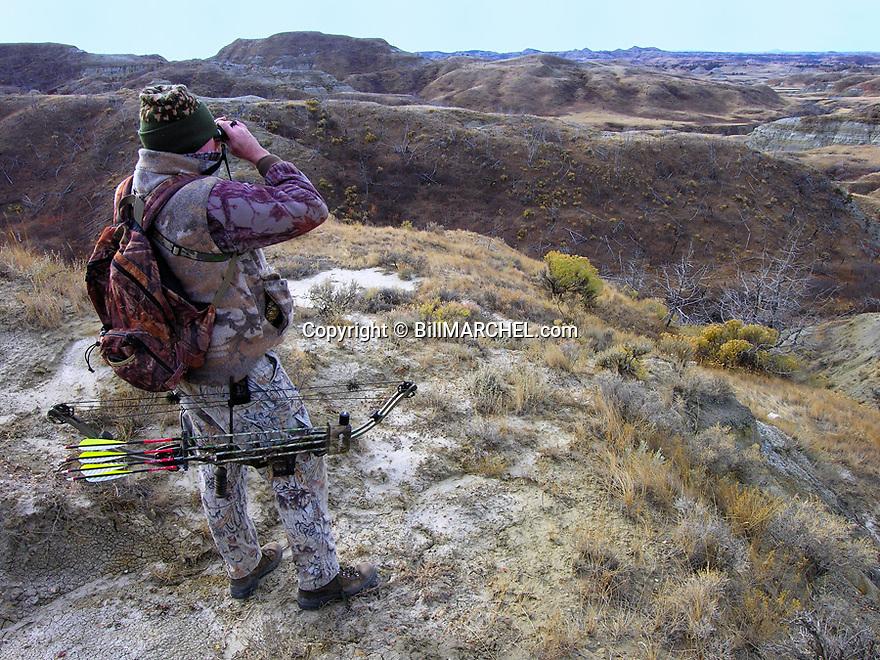 00105-047.01 Bowhunting: Archer scans distant slopes for game in arid Badlands type habitat.  Hunt, spot and stalk, mule deer.