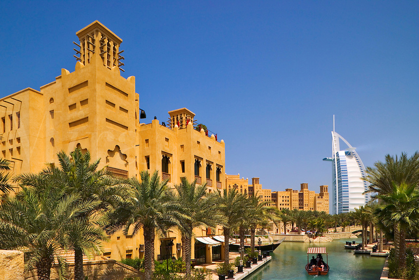 Madinat Jumeirah and the Burj al Arab Hotel, with an abra, a water taxi on the canal.  Dubai.  United Arab Emirates.