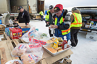 Volunteers take a short break to eat lunch at the Willow, Alaska airport during the Food Flyout on Saturday, February 20, 2016.  Iditarod 2016