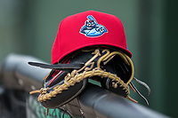 A Lakewood BlueClaws batting practice cap sits on top of a catcher's mitt outside the dugout prior to the game against the Kannapolis Intimidators at Kannapolis Intimidators Stadium on April 6, 2017 in Kannapolis, North Carolina.  The BlueClaws defeated the Intimidators 7-5.  (Brian Westerholt/Four Seam Images)