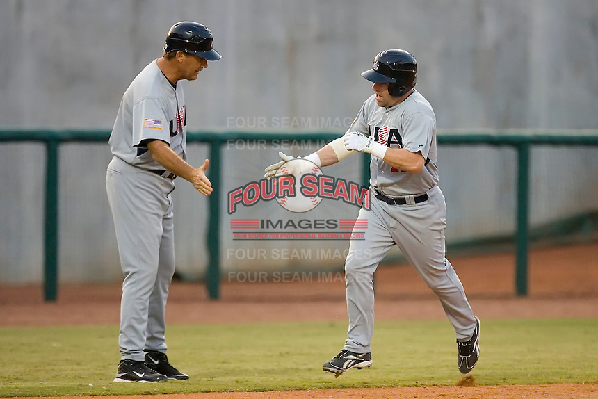 Jon Weber #11 of Team USA slaps hands with third base coach Jamie Quirk #9 after hitting a home run against Team Canada at the USA Baseball National Training Center, September 4, 2009 in Cary, North Carolina.  (Photo by Brian Westerholt / Four Seam Images)