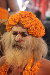 A sadhu takes a quiet moment amongst the crowds of chanting sadhus, moments before beginning the parade to the holy rivers.