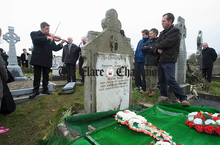 Liam O Connor, son of Mick O Connor, playing at the graveside of Joe Ryan in Inagh following the burial. Photograph by John Kelly.