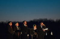 The pastor and lectors stand in a spotlight as worshippers gather for Easter sunrise services atop a dam at a reservoir.