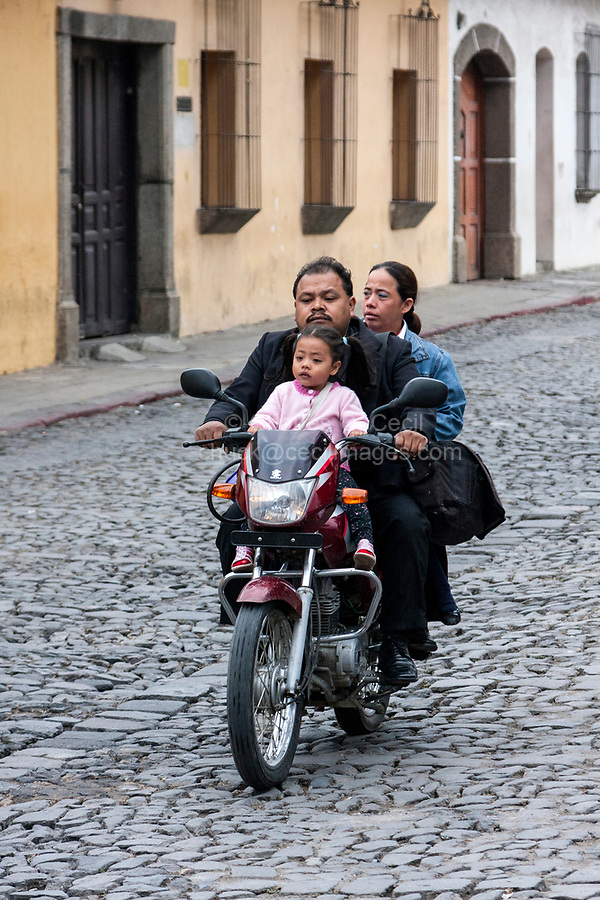 Antigua, Guatemala.  Parents Riding with Little Girl on Motorbike, no Helmet.