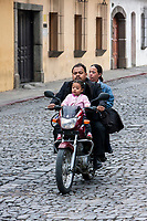 Antigua, Guatemala.  Parents Riding with Little Girl on Motorbike, no Helmet.