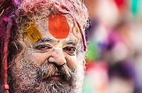 Smiling Hindu Sadhu holy man with his painted face covered in Holi celebration powder close-up portrait, in Mathura Uttar Pradesh India