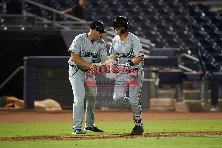 Surprise Saguaros Brewer Hicklen (23), of the Kansas City Royals organization, is congratulated by manager Scott Thorman (35) after hitting a home run to right field during an Arizona Fall League game against the Peoria Javelinas on September 22, 2019 at Peoria Sports Complex in Peoria, Arizona. Surprise defeated Peoria 2-1. (Zachary Lucy/Four Seam Images)