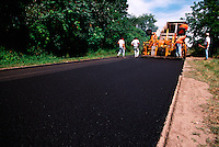 Road crew workers laying fresh pavement.