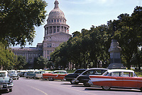 Vintage 1961 view of the Texas State Capitol and row of vintage american-made automobiles surrounded live oak trees that lead up to the capitol entrance. This is image is shot on 35mm Kodak color slide film.