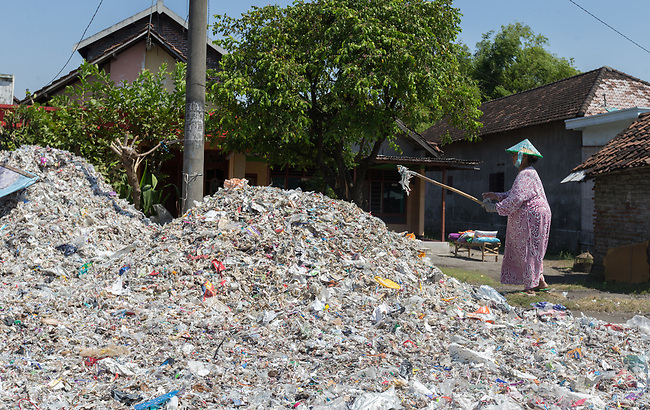 21 May 2019, Bangun Village,East Java, Indonesia: A local woman picks through plastic rubbish in Bangun Village outside Surabaya, Indonesia. Millions of tonnes of recyclable plastic trash from Australia and Europe is dumped for rag pickers to separate and sort. The plastics are used to fuel fires at local tofu factories among other industries. Australia is illegally sending non recyclable trash hidden within this lode and the Indonesian Government is cracking down on the practice and preparing to refuse to take Australia's rubbish that is creating environmental and health issues locally. Picture by Graham Crouch/The Australian