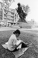 April 1970, Ho Chi Minh City, Vietnam --- A Vietnamese woman sews cloth in front of a statue of two soldiers in a park in Saigon. --- Image by © JP Laffont
