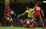 Australia wing Joe Tomane looks for support as he's tackled by Sam Warburton.<br /> Dove Men Series 2014<br /> Wales v Australia<br /> Millennium Stadium<br /> 08.11.14<br /> ©Steve Pope-SPORTINGWALES