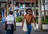 Urban Street Photograph of a local surfer carrying his surfboard along the Malecon in Puerto Vallarta, Mexico.